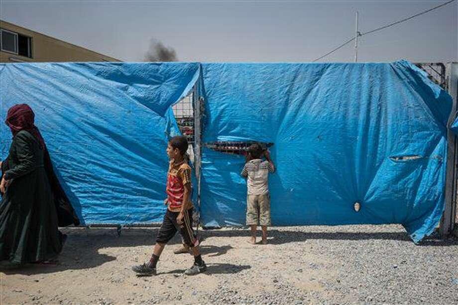 ARCHIVO - En esta foto de archivo del 7 de agosto de 2016, un niño espía a través de una cerca en torno al campamento de Dibaga para civiles desplazados en Irak. Más de 100.000 personas se han visto desplazadas conforme las fuerzas iraquíes despejan el terreno para la crucial batalla por Mosul, tomada por el grupo Estado islámico, según dijo el viernes 12 de agosto de 2016 la agencia de refugiados de la ONU. (AP Foto/Alice Martins, File) Photo: Alice Martins