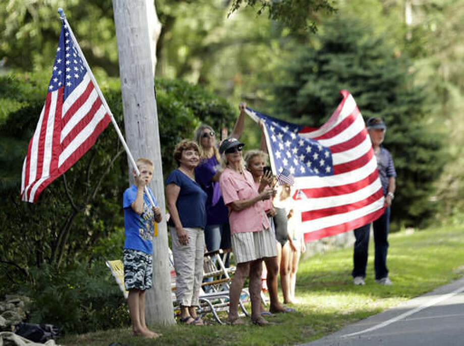 People wave the American flag as the presidential motorcade passes in White Haven, Mass., on Martha's Vineyard, Thursday, Aug. 11, 2016. (AP Photo/Manuel Balce Ceneta) Photo: Manuel Balce Ceneta