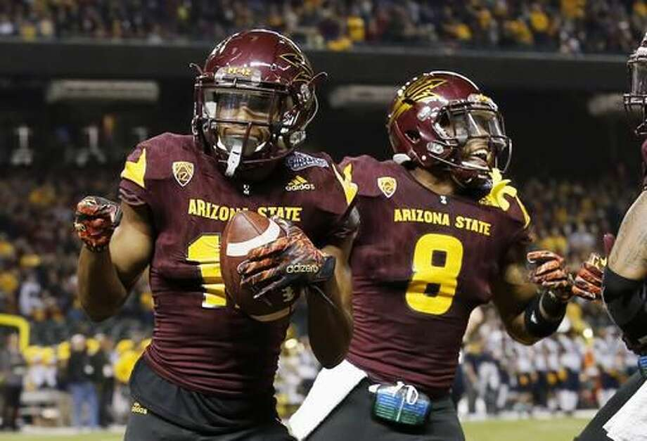 FILE - In this Jan. 2, 2016, file photo, Arizona State receiver Tim White, left, celebrates with teammate Lloyd Carrington after scoring two points after returning a blocked extra-point kick against West Virginia during the first half of the Cactus Bowl NCAA college football game in Phoenix, Ariz. (AP Photo/Ross D. Franklin, file) Photo: Ross D. Franklin