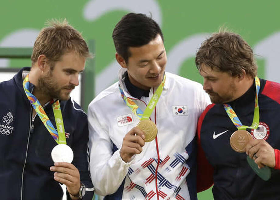 Gold medal winner Ku Bon-chan of South Korea, center, celebrates on the podium with silver medalist Jean Charles Valladont, left, and bronze medalist Brady Ellison of the United States at the awards ceremony of the men's individual archery competition at the Sambadrome venue during the Summer Olympics in Rio de Janeiro, Brazil, Friday, Aug. 12, 2016. (AP Photo/Alessandra Tarantino) Photo: Alessandra Tarantino