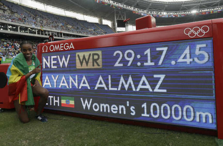Ethiopia's Almaz Ayana poses next to a scoreboard showing her new world record in the women's 10,000-meter final during the Summer Olympics in Rio de Janeiro, Brazil, Friday, Aug. 12, 2016. (AP Photo/Matt Slocum) Photo: Matt Slocum