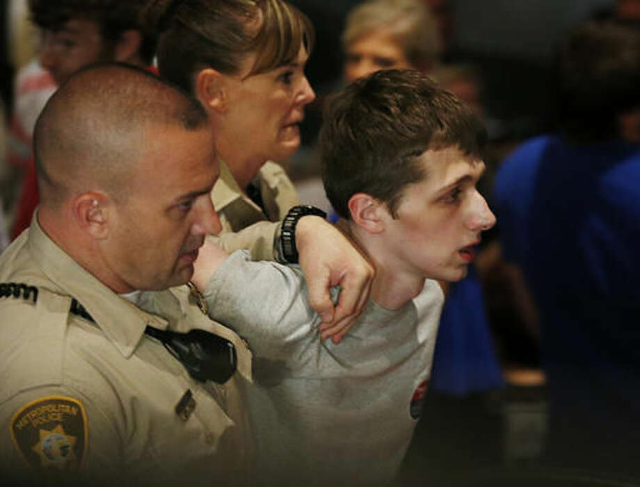 FILE - In this June 18, 2016, photo, police remove Michael Sandford as Republican presidential candidate Donald Trump speaks at the Treasure Island hotel and casino in Las Vegas. Sanford's mother is asking a U.S. judge to let her personally visit her son, who is jailed in Nevada after what authorities say was an an attempt to shoot Trump at a Las Vegas campaign rally. (AP Photo/John Locher, File) Photo: John Locher