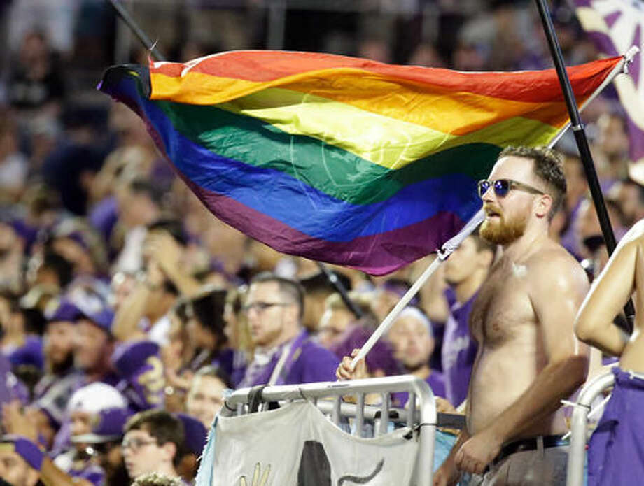 In this Sunday, July 31, 2016 photo, Major League soccer fans show solidarity with Pulse shooting victims by waving rainbow colored flags at a match in Orlando, Fla. In the aftermath of the Pulse nightclub shootings, the rainbow colors are appearing all over metro Orlando. (AP Photo/John Raoux) Photo: John Raoux