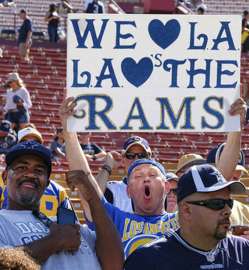 A Los Angeles Rams fan displays a sign while waiting for his team to arrive at Los Angeles Memorial Coliseum on Saturday, Aug. 13, 2016. Los Angeles fans celebrate the return of the NFL and their long-lost Los Angeles Rams to the city at the team's first preseason NFL game against the Dallas Cowboys. (AP Photo/Richard Vogel) Photo: Richard Vogel