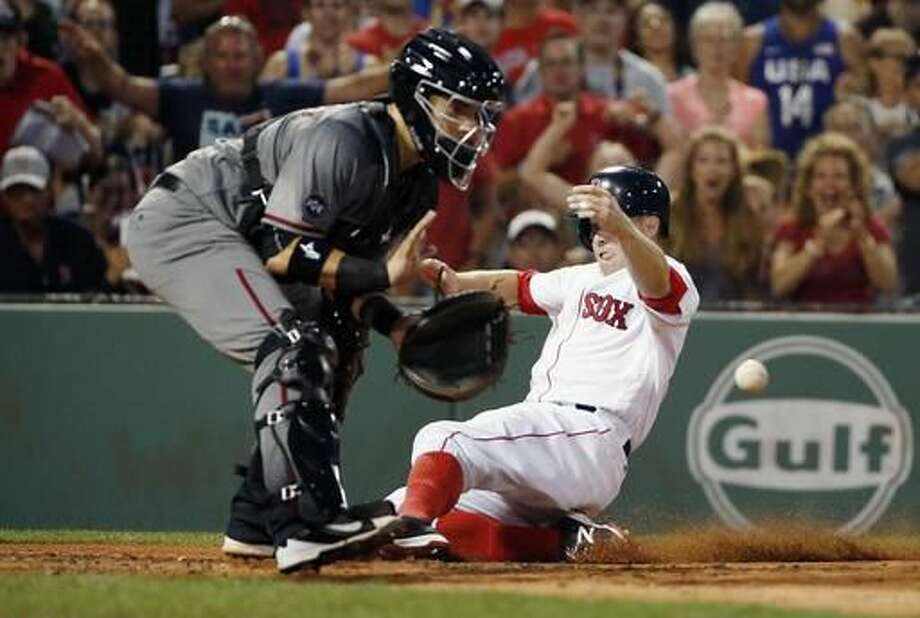 Boston Red Sox's Brock Holt, right, scores on a single by Dustin Pedroia as Arizona Diamondbacks' Oscar Hernandez gets the throw during the third inning of a baseball game in Boston, Saturday, Aug. 13, 2016. (AP Photo/Michael Dwyer) Photo: Michael Dwyer