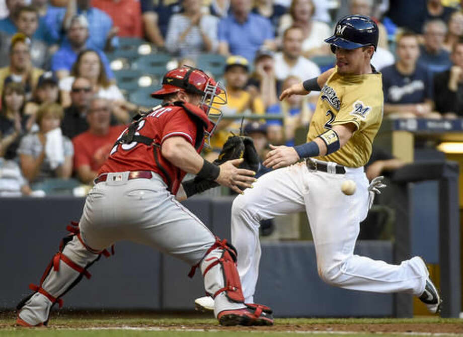 Milwaukee Brewers' Scooter Gennett, right, tries to score on a double by Hernan Perez before being tagged out by Cincinnati Reds catcher Tucker Barnhart, left, during the fourth inning of a baseball game Saturday, Aug. 13, 2016, in Milwaukee. (AP Photo/Benny Sieu) Photo: Benny Sieu