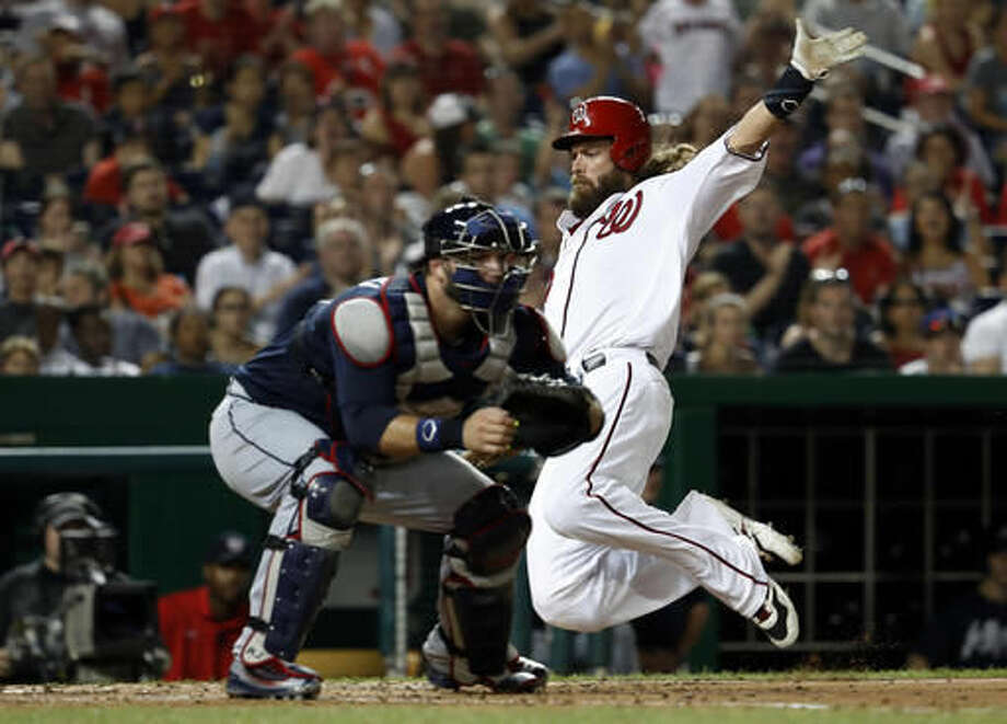 Washington Nationals' Jayson Werth, right, leaps to slide into home to score off a single hit by teammate Danny Espinosa as Atlanta Braves catcher A.J. Pierzynski, left, waits for the throw during the sixth inning of a baseball game at Nationals Park, Saturday, Aug. 13, 2016, in Washington. (AP Photo/Carolyn Kaster) Photo: Carolyn Kaster