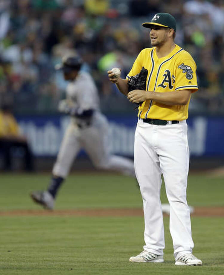 Oakland Athletics pitcher Kendall Graveman, right, waits for Seattle Mariners' Robinson Cano, left, to run the bases after Cano hit a two-run home run in the fifth inning of a baseball game Saturday, Aug. 13, 2016, in Oakland, Calif. (AP Photo/Ben Margot) Photo: Ben Margot
