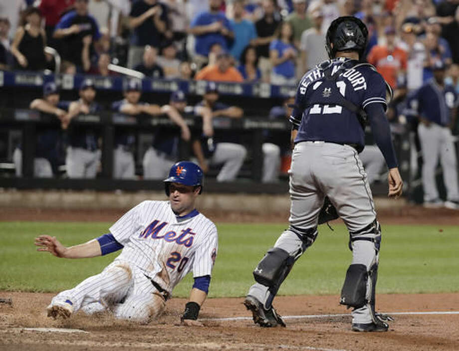 New York Mets second baseman Neil Walker (20) slides home safely to score the winning run on a ground ball fielder's choice hit by Wilmer Flores to San Diego Padres second baseman Ryan Schimpf during the eleventh inning of a baseball game, Saturday, Aug. 13, 2016, in New York. The Mets won 3-2. (AP Photo/Julie Jacobson) Photo: Julie Jacobson