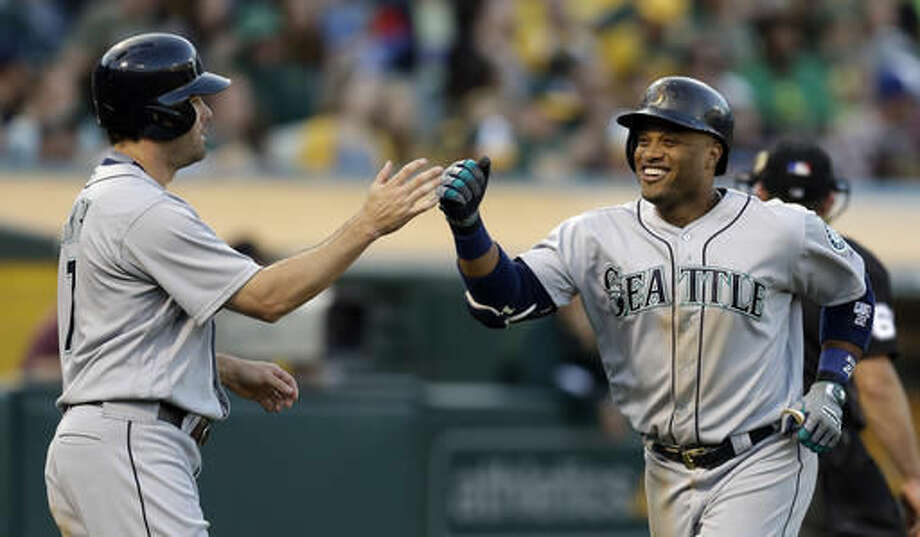 Seattle Mariners' Robinson Cano, right, celebrates with Seth Smith (7) after hitting a two run home run off Oakland Athletics' Kendall Graveman in the fifth inning of a baseball game Saturday, Aug. 13, 2016, in Oakland, Calif. (AP Photo/Ben Margot) Photo: Ben Margot