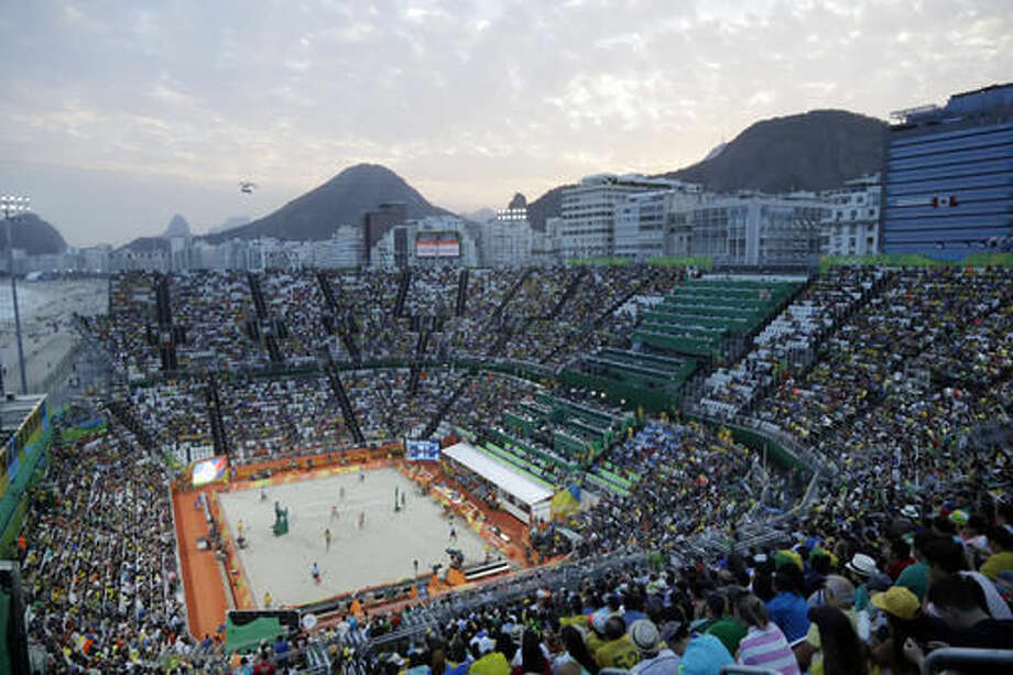The sun sets over the Olympic beach volleyball arena during a women's beach volleyball match between Brazil and United States at the 2016 Summer Olympics in Rio de Janeiro, Brazil, Tuesday, Aug. 9, 2016. (AP Photo/Marcio Jose Sanchez)The sun sets over Copacabana beach and the Olympic beach volleyball arena during a women's beach volleyball match between Brazil and United States at the 2016 Summer Olympics in Rio de Janeiro, Brazil, Tuesday, Aug. 9, 2016. (AP Photo/Marcio Jose Sanchez) Photo: Marcio Jose Sanchez