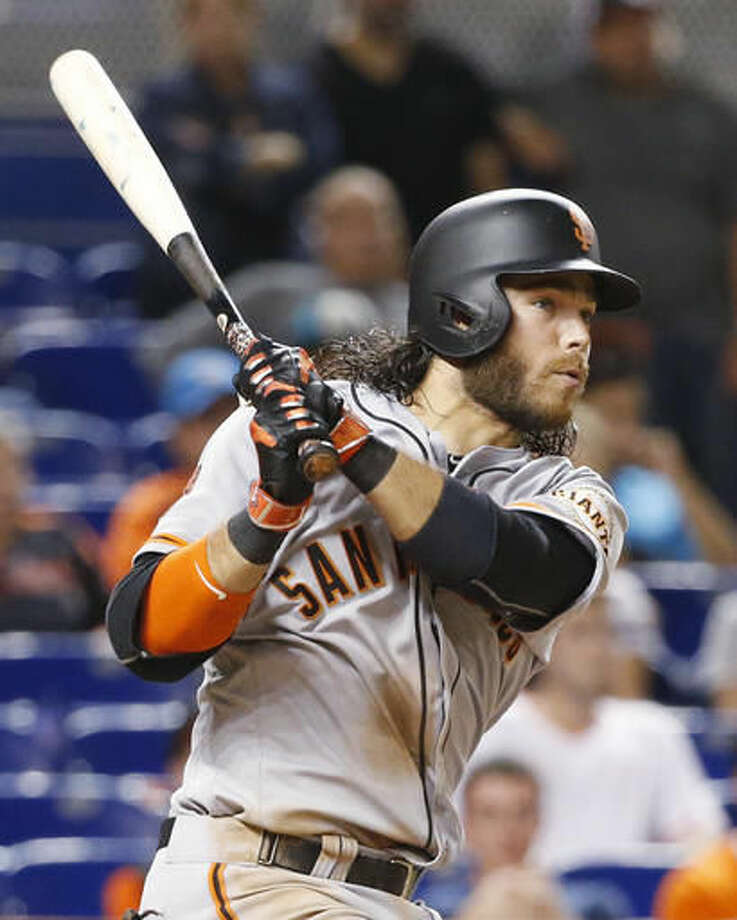 San Francisco Giants' Brandon Crawford watches the ball as he hits a triple during the 13th inning of a baseball game against the Miami Marlins, Monday, Aug. 8, 2016, in Miami. The Giants defeated the Marlins 8-7 early Tuesday, in 14 innings. Crawford became the first major league player in 41 years to get seven hits in a game. (AP Photo/Wilfredo Lee) Photo: Wilfredo Lee