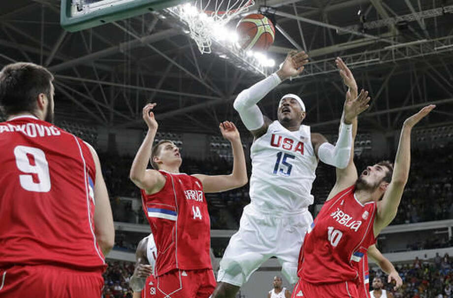 United States' Carmelo Anthony (15) fouled as he drives to the basket between Serbia's Nikola Jokic (14) and Nikola Kalinic (10) is during a men's basketball game at the 2016 Summer Olympics in Rio de Janeiro, Brazil, Friday, Aug. 12, 2016. (AP Photo/Eric Gay) Photo: Eric Gay