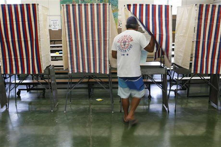 A voter enters a both at a polling place during the Hawaii primary at Kawananakoa Middle School, Saturday, Aug. 13, 2016, in Honolulu. Hawaii voters headed to the polls Saturday to decide who will get their party nominations and advance to the general election in congressional and local races. (AP Photo/Marco Garcia) Photo: Marco Garcia