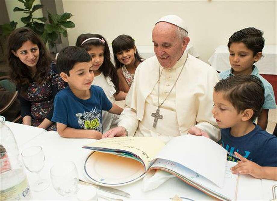 El papa Francisco observa algunos dibujos acompañado de niños de familias refugiadas, el jueves 11 de agosto de 2016, en el Vaticano. (L'Osservatore Romano/Fotografía Pool vía AP) Photo: Uncredited
