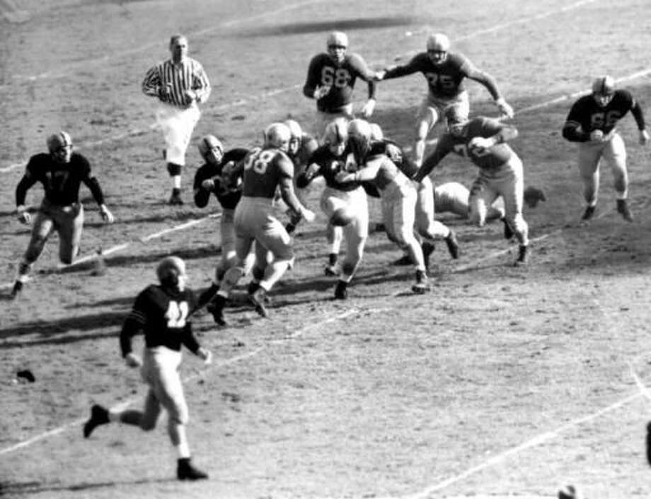 "FILE - In this Nov. 9, 1946, file photo, Army fullback Felix ""Doc"" Blanchard (35), center left in front of the official, fumbles the ball, in air at center, during the first half against Notre Dame, at Yankee Stadium in New York. Teammate Glen Davis (41), left foreground, recovered the ball. Identifiable Notre Dame players are Bill Fischer (72) and Jim Martin (38). (AP Photo/File) Photo: Anonymous"