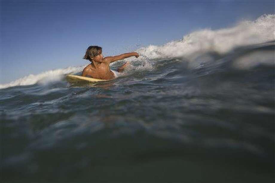 Eric Marques nada para agarrar una ola mientras toma clases de surf en la playa Sao Conrado de Río de Janeiro el sábado, 13 de agosto de 2016. Marques toma clases en la Escuela de Surf dfe Rocinha. (AP Photo/Felipe Dana) Photo: Felipe Dana