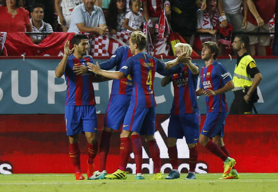 Barcelona's Luis Suarez, left, celebrates with teammates after scoring the first goal during the Spanish Super Cup first=leg soccer match, against Sevilla, at Ramon Sanchez-Pizjuan stadium in Seville, Spain, Sunday, Aug. 14, 2016. (AP Photo/Antonio Pizarro) Photo: Antonio Pizarro