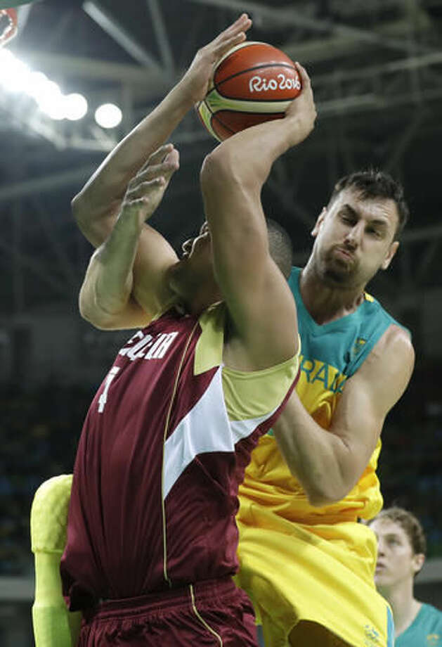 Venezuela's Miguel Marriaga (4) is fouled by Australia's Andrew Bogut, right, during a basketball game at the 2016 Summer Olympics in Rio de Janeiro, Brazil, Sunday, Aug. 14, 2016. (AP Photo/Charlie Neibergall) Photo: Charlie Neibergall