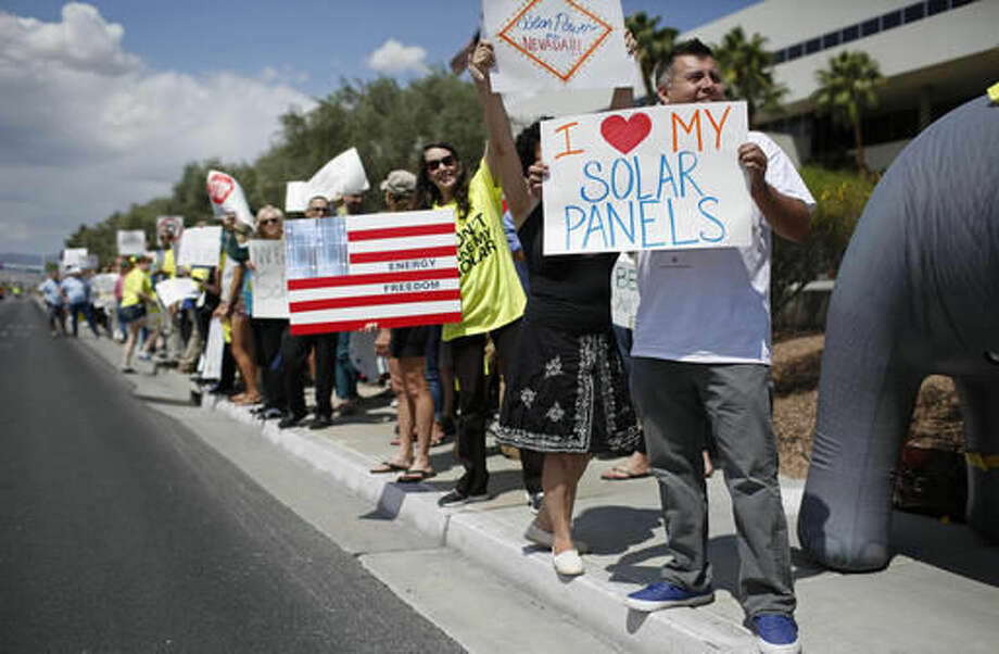 FILE--In this April 22, 2015, file photo, protestors, including Ronald Brittan, right, line up along the street during a rally in front of NV Energy in Las Vegas. Rooftop solar advocates had hoped to take their cause directly to voters in 2016 after a rate hike this year rocked the industry in Nevada. But in spite of broad voter interest in a sweeping referendum, the Nevada Supreme Court ruled it was unfit for a statewide vote. Now, the pro-solar forces are setting their sights on a more circuitous route through the Nevada Legislature. (AP Photo/John Locher, File) Photo: John Locher