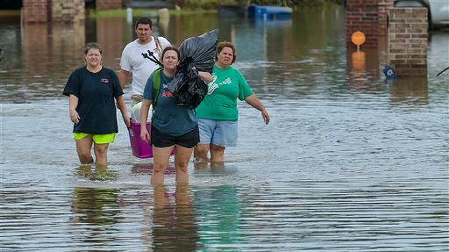 People wade in water near flood damaged homes in Highland Ridge Subdivision in Youngsville, La., Sunday, Aug. 14, 2016. Torrential rains swamped parts of southern Louisiana, causing widespread flooding. (Scott Clause/The Daily Advertiser via AP) Photo: Scott Clause