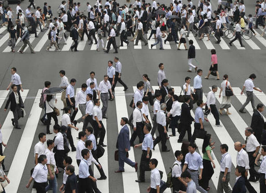 In this July 1, 2016 photo, people cross a street in Tokyo, Friday, July 1, 2016. Japan's economy grew at a slower than forecast 0.2 percent annual rate in the April-June quarter, as the recovery was sapped by weaker exports and business investment, the government said Monday, Aug. 15, 2016. (AP Photo/Koji Sasahara) Photo: Koji Sasahara