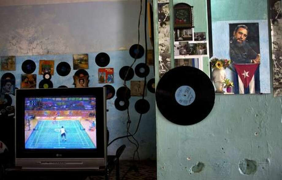 In this Aug. 13, photo, a poster with the image of the Cuban leader Fidel Castro is reflected on a mirror, right, as a TV shows the Rio Olympic Games at a house in Havana, Cuba. As Castro celebrates his 90th birthday, the Cuban government has taken a low-key approach to commemorating the day. There are no massive rallies or parades planned. (AP Photo/Ramon Espinosa) Photo: Ramon Espinosa
