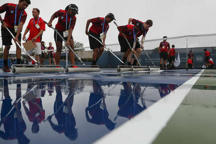 Volunteers prepare the court after rain delayed the opening of the Western & Southern Open tennis tournament, Sunday, Aug. 14, 2016, in Mason, Ohio. (AP Photo/John Minchillo) Photo: John Minchillo