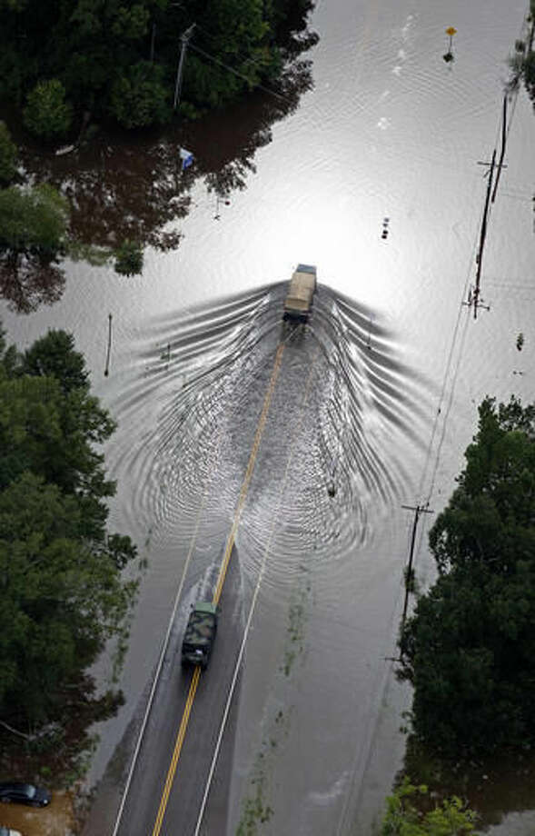 In this aerial photo over Robert, La., Army National Guard, vehicles drive on flooded U.S. Route 190 after heavy rains inundated the region, Saturday, Aug. 13, 2016. Louisiana Gov. John Bel Edwards says more than 1,000 people in south Louisiana have been rescued from homes, vehicles and even clinging to trees as a slow-moving storm hammers the state with flooding. (AP Photo/Max Becherer) Photo: Max Becherer