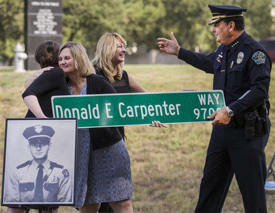 In this Aug. 13, 2016 photo, Austin City Council member Ellen Troxclair, right, embraces Donna Carpenter Aleman, second from right, as Cheryl Carpenter, center, is welcomed by Austin Police Chief Art Acevedo during a sign unveiling honoring Officer Don Carpenter, in Austin, Texas. Carpenter was responding to a burglary and was shot and killed in South west Austin on Jan. 28 1964. (Ricardo Brazziell, Austin American-Statesman via AP) Photo: Ricardo Brazziell