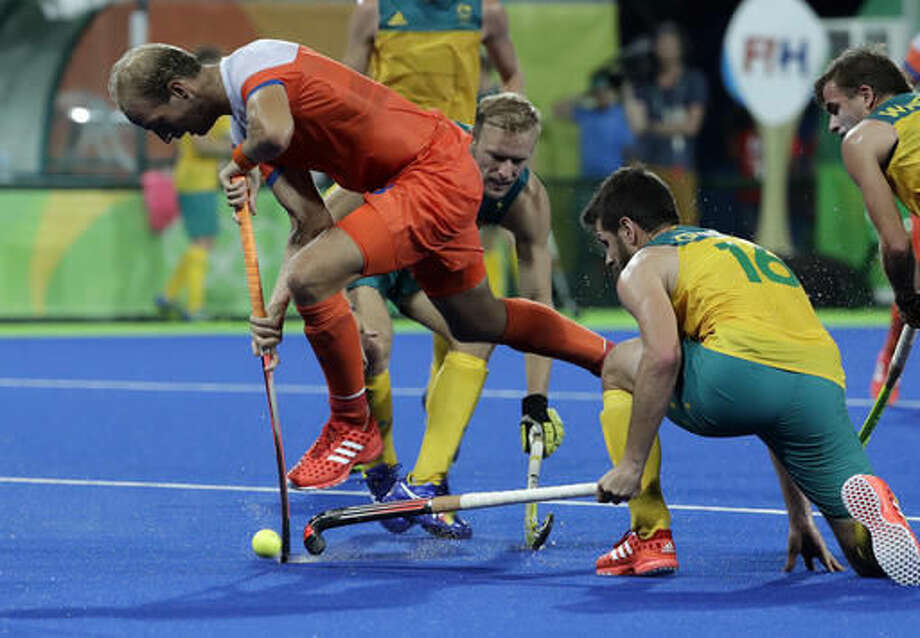 Netherlands' Billy Bakker, center, fight for the ball with Australia's Matt Ghodes, right, during a men's field hockey quarterfinal match at 2016 Summer Olympics in Rio de Janeiro, Brazil, Sunday, Aug. 14, 2016. (AP Photo/Hussein Malla) Photo: Hussein Malla