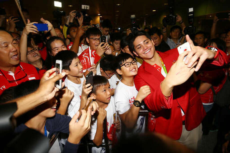 Singaporean swimmer Joseph Schooling, front right, poses for a photo with people at the Singapore Changi Airport in Singapore Monday, Aug. 15, 2016. Schooling won gold medal in the men's 100-meter butterfly and made history by winning the country's first gold medal at the 2016 Summer Olympics in Rio de Janeiro, Brazil. (AP Photo/Yong Teck Lim) Photo: Yong Teck Lim