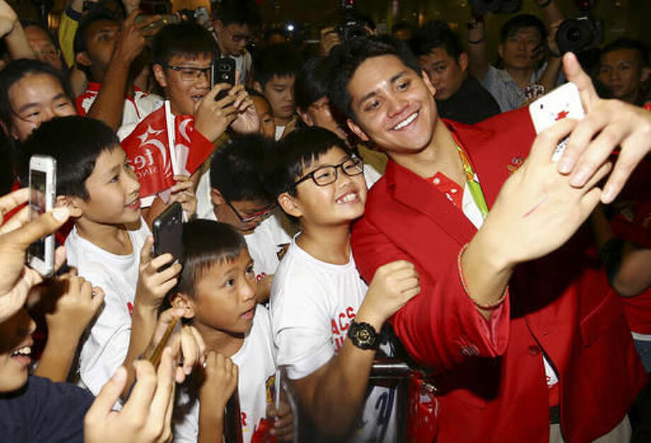 Singaporean swimmer Joseph Schooling, right, poses for a selfie as he arrives at Singapore Changi Airport in Singapore, Monday, Aug. 15, 2016. Schooling won the gold medal in the men's 100-meter butterfly and made history by winning the country's first gold medal at the 2016 Summer Olympics in Rio de Janeiro, Brazil. (AP Photo/Yong Teck Lim) Photo: Yong Teck Lim