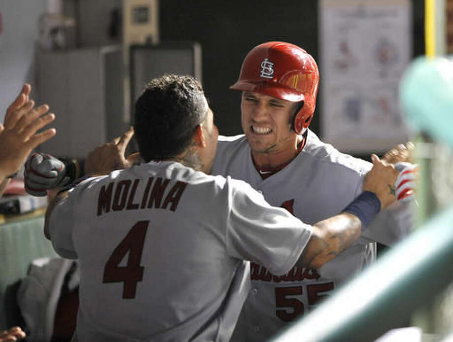 St. Louis Cardinals' Stephen Piscotty (55) celebrates with teammate Yadier Molina (4) in the dugout after hitting a three-run home run during the eighth inning of a baseball game against the Chicago Cubs Sunday, Aug. 14, 2016, in Chicago. (AP Photo/Paul Beaty) Photo: Paul Beaty