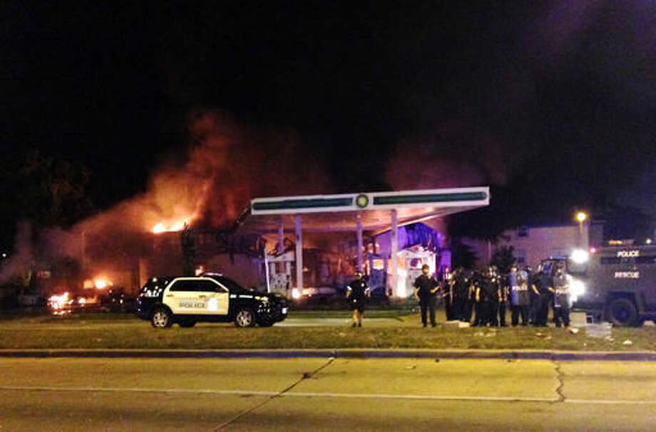 Authorities respond near a burning gas station as dozens of people protest following the fatal shooting of a man in Milwaukee, Saturday, Aug. 13, 2016. A crowd of protesters skirmished with police Saturday night in the Milwaukee neighborhood where an officer shot and killed a man after a traffic stop and foot chase earlier in the day, setting fire to a police car and torching a gas station. (AP Photo/Gretchen Ehlke) Photo: Gretchen Ehlke