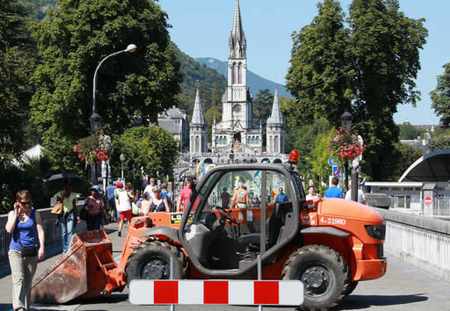 Authority blocks with a bulldozer one of the entries to the site of the sanctuary in Lourdes, southwestern France, Sunday Aug.14, 2016. Security measures for Lourdes' biggest annual event, the Feast of the Assumption, have been increased as France, on edge with fears of a new terror attack, continues to cancel festive and sports events for security reasons. (AP Photo/Bob Edme) Photo: Bob Edme