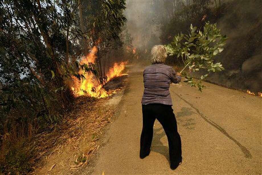 Una mujer uses una ramma para tratar de combatir un incendio en un camino que lleva al poblado de Parada, Portugal, el jueves 11 de agosto de 2016. (AP Foto/Sergio Azenha) Photo: Sergio Azenha