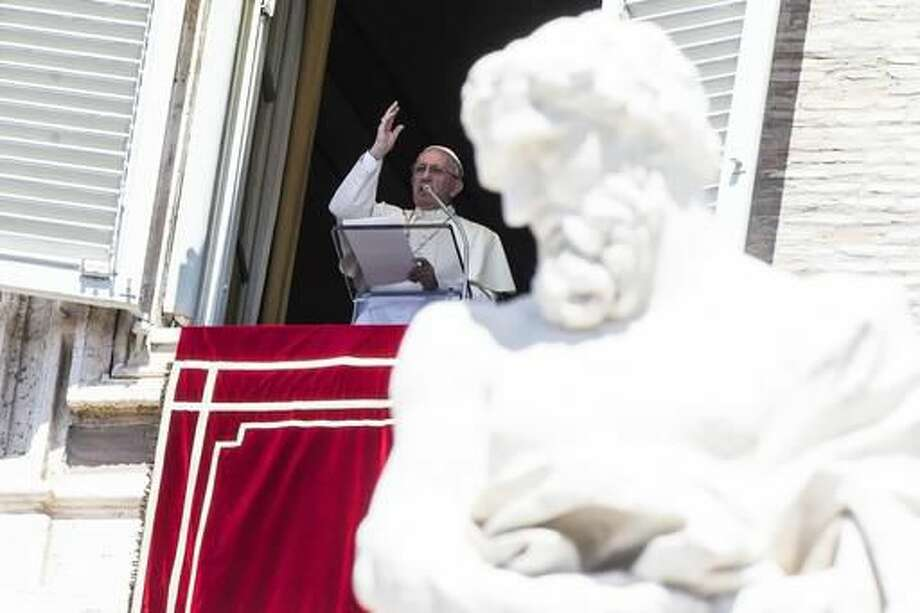 """Pope Francis waves to faithful from the window of his studio overlooking St. Peter's Square, at the Vatican Monday, Aug. 15, 2016. Pope Francis is urging people to think about the plight of women who are """"slaves of the arrogance of the powerful"""" as well as children forced to do """"inhumane"""" work. In remarks to tourists and pilgrims in St. Peter's Square Monday, Francis decried that some women """"are obliged to surrender in body and spirit to the covetousness of men."""" (Angelo Carconi/ANSA via AP) Photo: Angelo Carconi"""