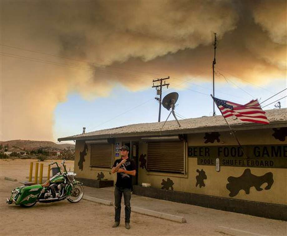 Moments before evacuation, Trevor Rainwater watches a wildfire burn into Summit Valley from the Joshua Inn in Hesperia Calif., on Sunday, Aug. 7, 2016. The fire, which broke out Sunday afternoon in the San Bernardino National Forest, prompted the evacuation order of the sparsely populated Summit Valley area east of the dam. (James Quigg/The Daily Press via AP) Photo: James Quigg
