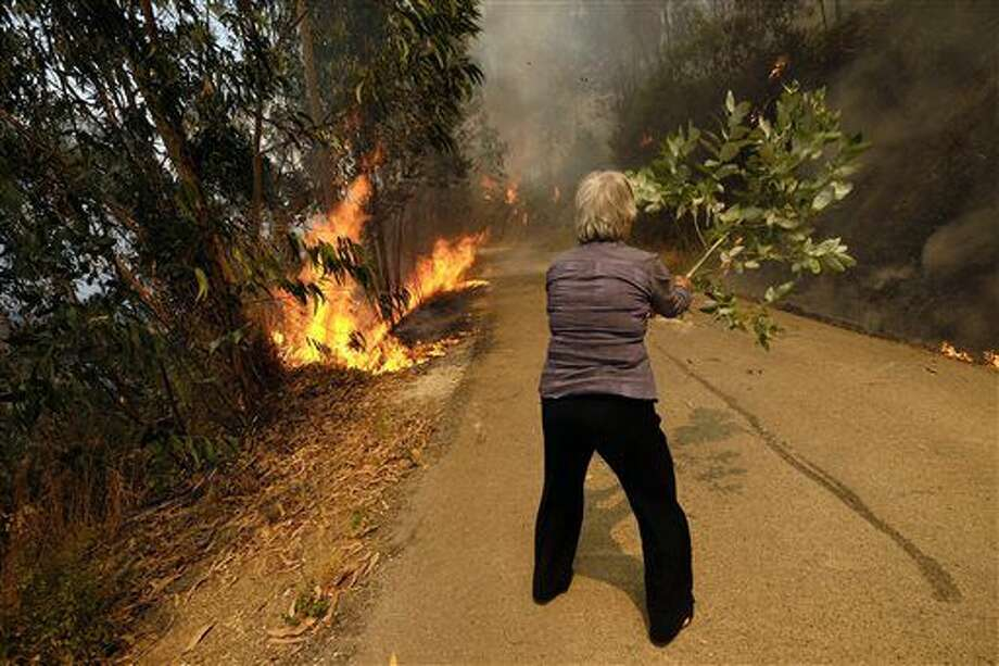 A woman uses a tree branch to fight a fire on a road leading to the village of Parada, northern Portugal, near Mortagua, on Thursday, Aug. 11 2016. Multiple blazes have been fed by brush in a hot, dry summer for several days. Major fires have also been raging in northwestern Spain and southern France. (AP Photo/Sergio Azenha) Photo: Sergio Azenha