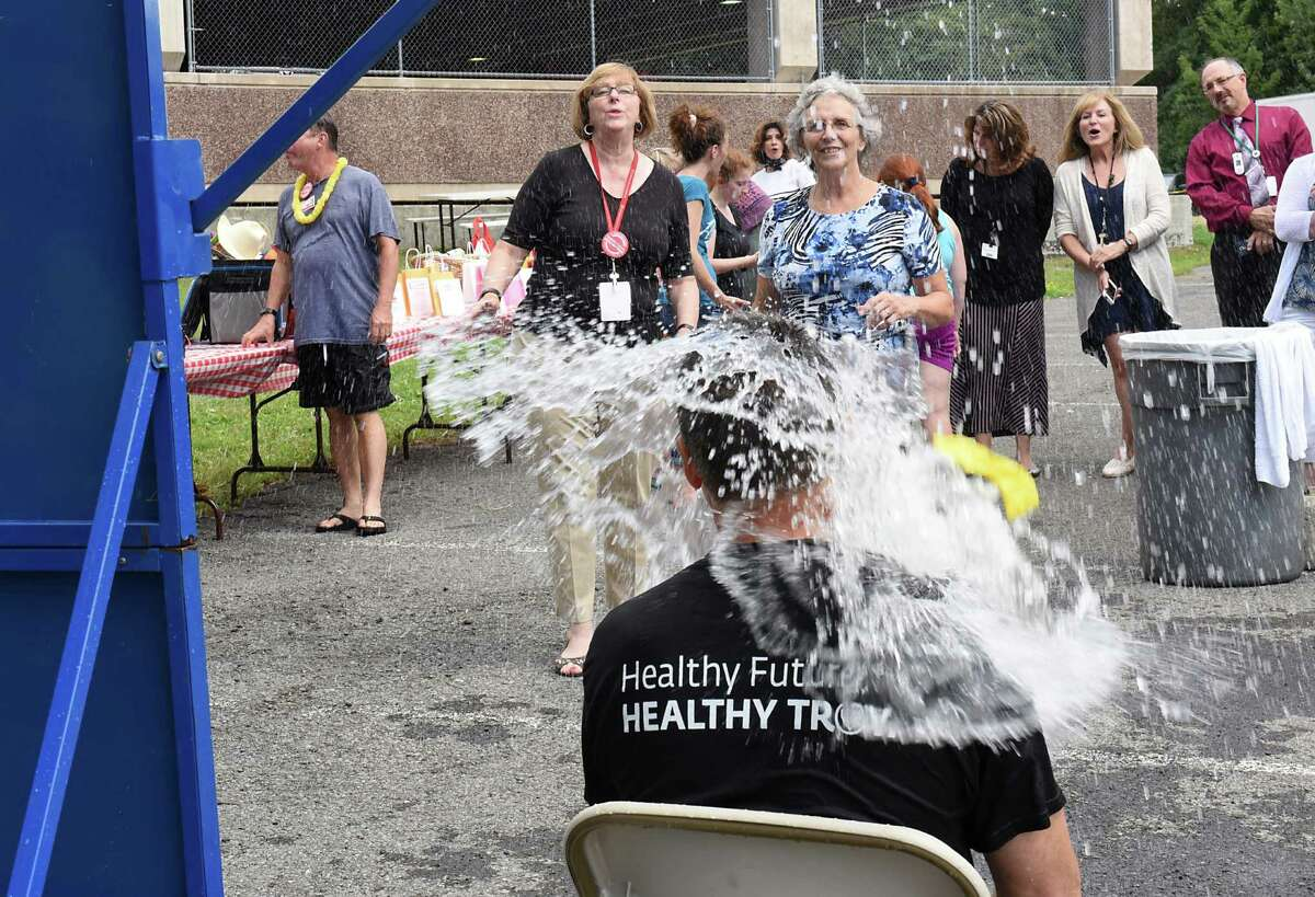 Sue Vitolins, director of patient safety and quality improvement, center in blue, gets Dr. Daniel Silverman, Chief Medical Officer and Vice President at at St. Peter's Health Partners, wet after hitting the target at a dunk the CEO event being held during the company picnic at at St. MaryOs Hospital on Wednesday, Aug. 17, 2016 in Troy, N.Y. (Lori Van Buren / Times Union)