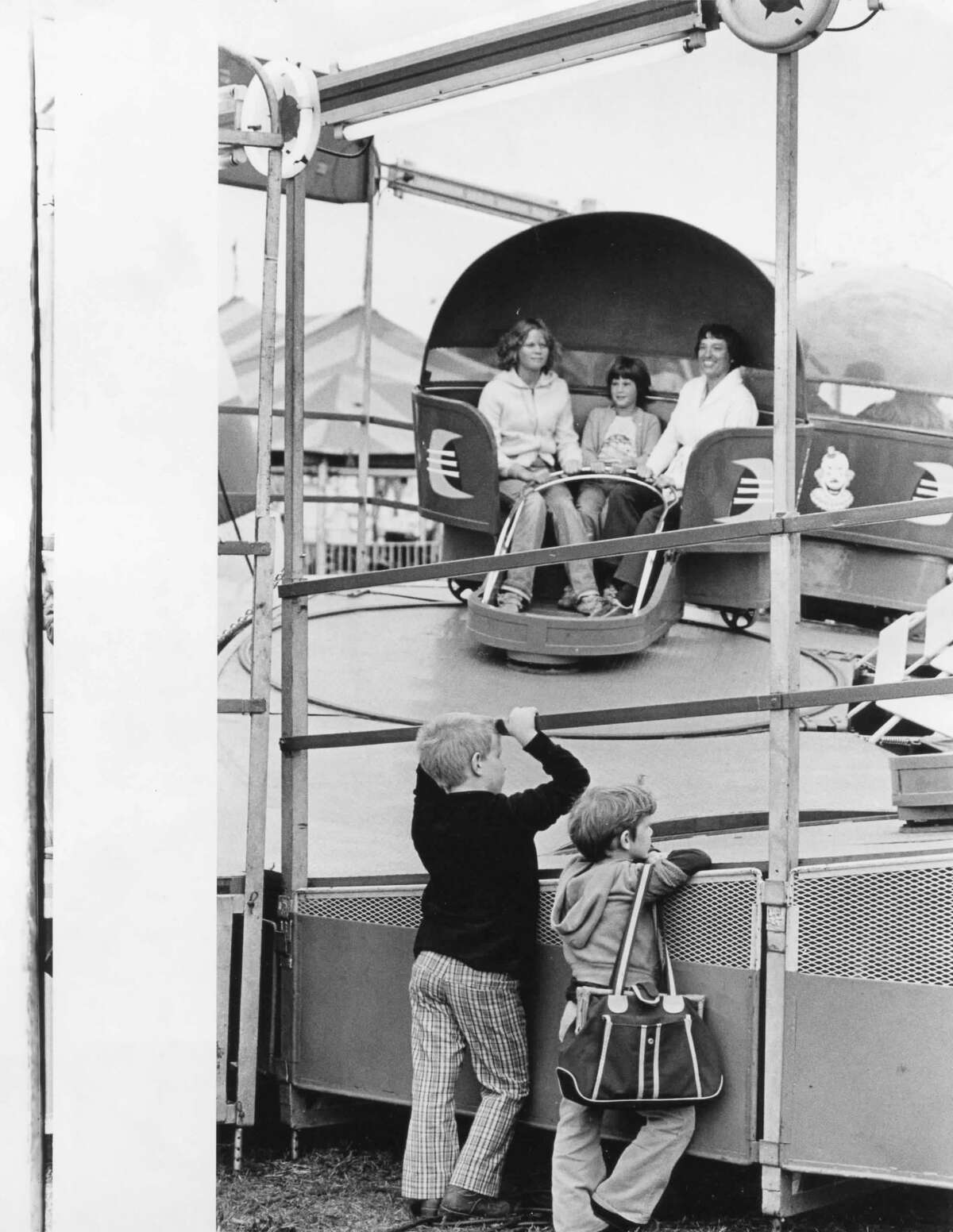 Michael and Charles Varner of Beaverton seem entranced with the tilting, whirling motion of one of the rides. August 1979