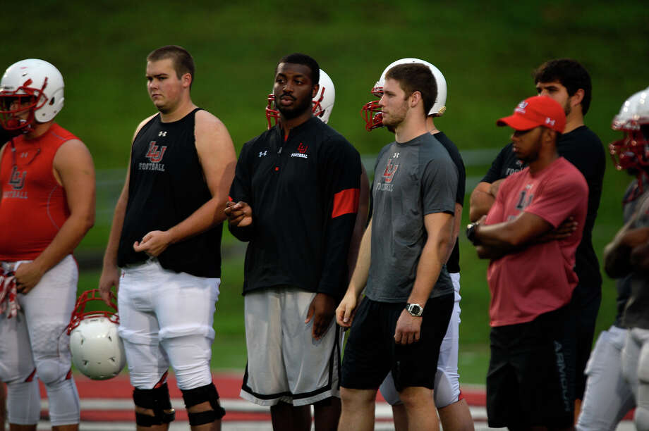 Justin Brock, a graduate assistant with Lamar's football team, watches the offensive line during a rainy practice on Monday evening.  Photo taken Monday 8/15/16 Ryan Pelham/The Enterprise Photo: Ryan Pelham / ©2016 The Beaumont Enterprise/Ryan Pelham