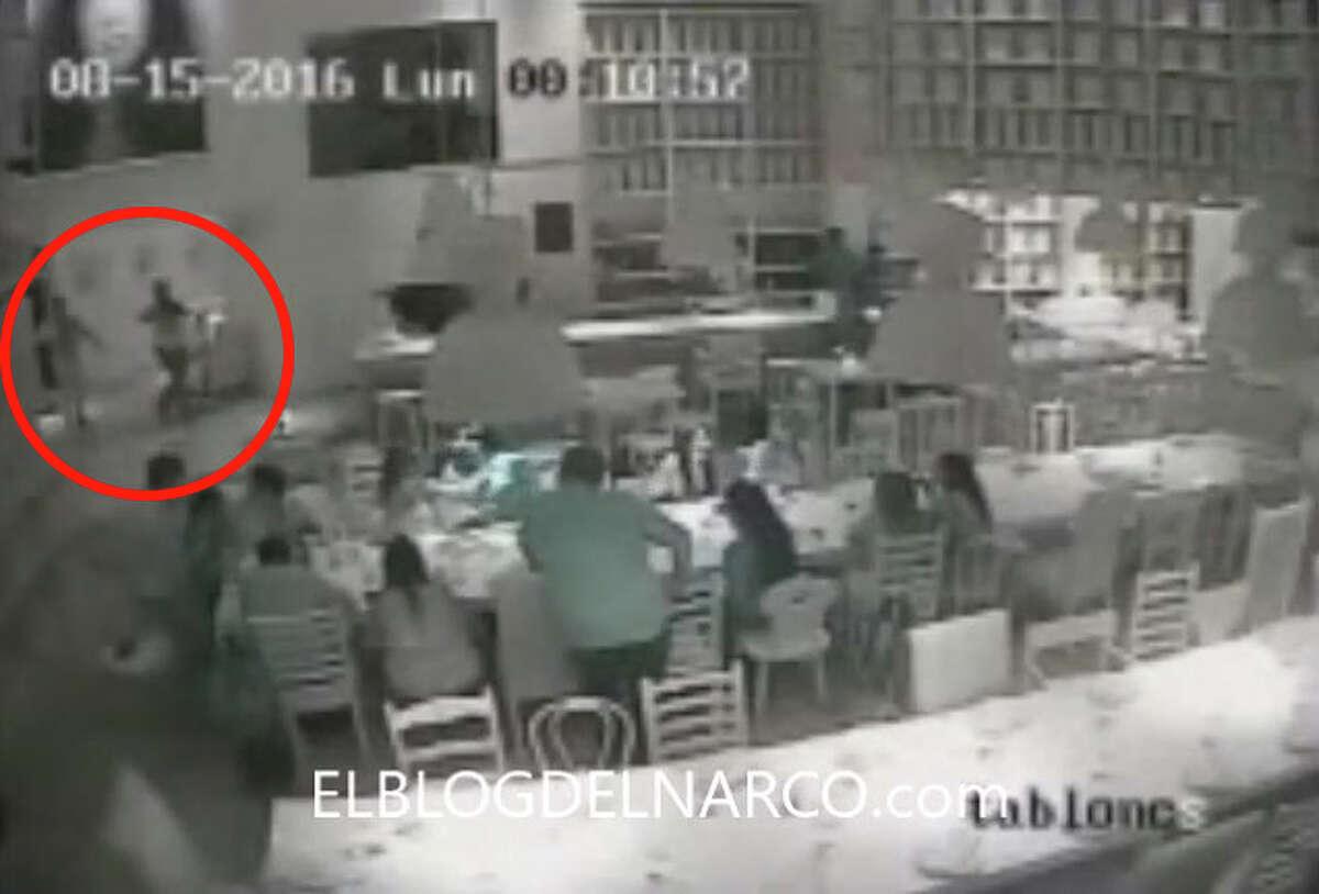 "In this still, gunmen enter the restaurant. Surveillance camera stills posted by Blog del Narco on Wednesday, August 17, 2016, purportedly show the armed abduction of Jesus Alfredo Guzman Salazar, the son of Sinaloa Cartel kingpin Joaquin ""El Chapo"" Guzman."