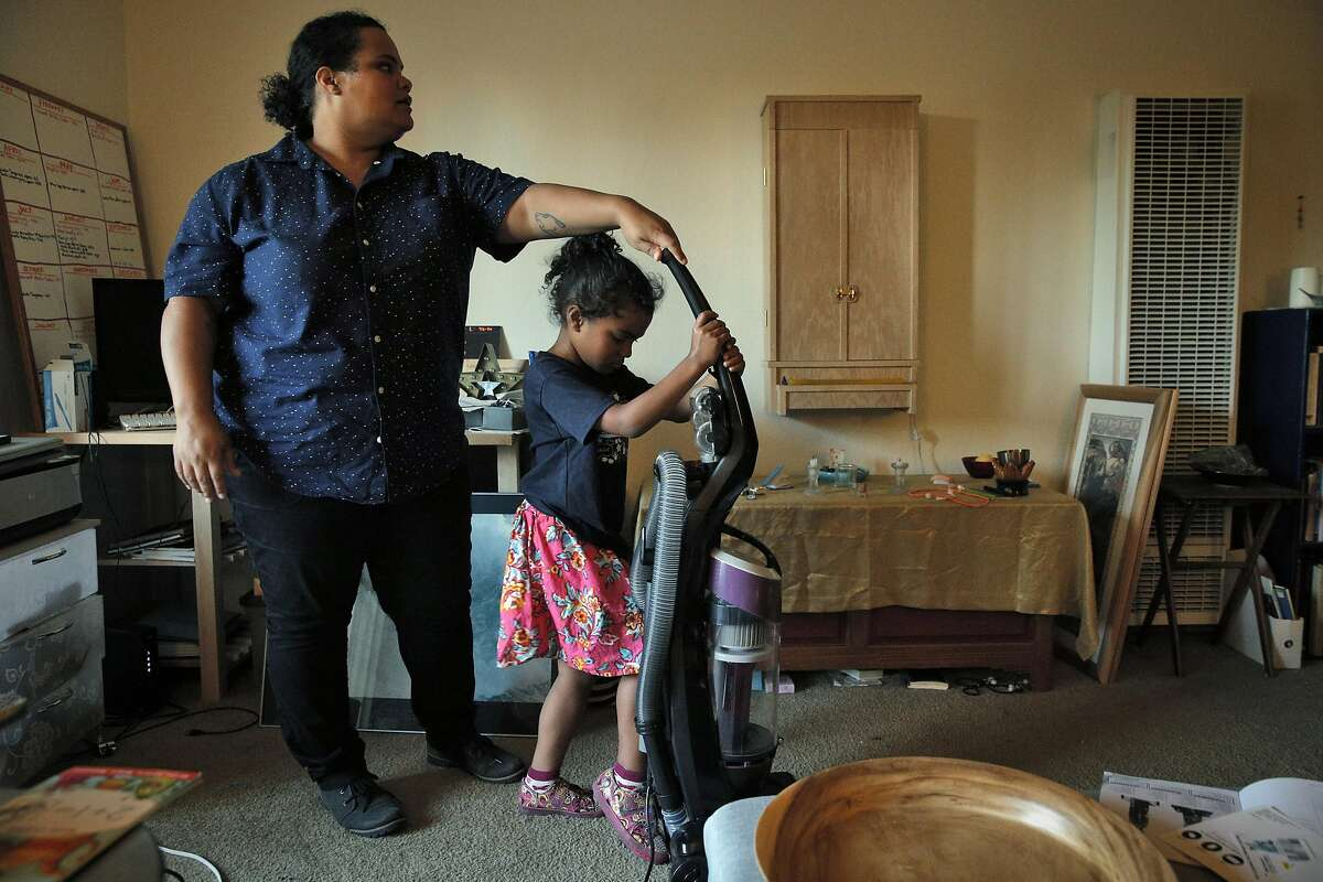 Amber Flame and her daughter, Evelia Taylor, 7, try out their new vacuum that they received through the Reparations.me website, at their Concord, Calif., apartment on Tuesday, August 16, 2016. The website began as a social experiment to help people of color when they need a hand.