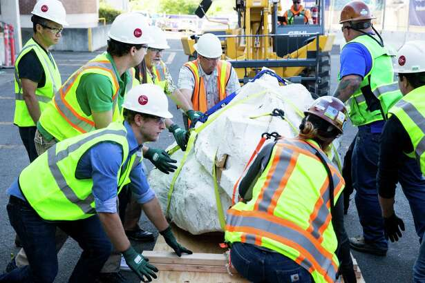 Crews work to move the Burke Museum of Natural History and Culture's new Tyrannosaurus rex skull, wrapped in a protective jacket, onto their loading dock on Thursday, Aug. 18, 2016.