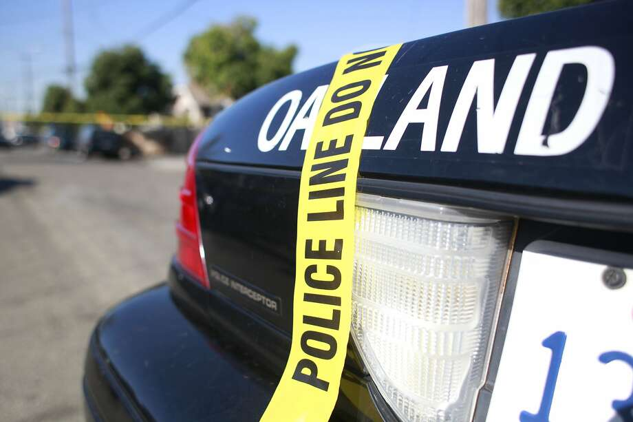 A police car blocks the street as Investigators with the Oakland Police Department gather evidence at the scene of a double homicide on the 1600 block of 72nd Avenue on Tuesday Oct. 2, 2012 in Oakland, Calif. Theses killings mark the fourth during a 24 hours period in Oakland. Photo: Mike Kepka, The Chronicle