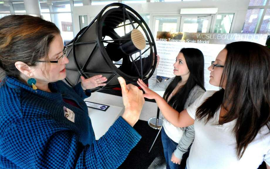 """Helen Bechard of Western Connecticut State University, left, tells Jessica Morfea, center, a freshman from Mahopac, N.Y., and Alyssa Groski, a junior from Danbury, about a scale model of the Hubble telescope during a """"Women in Science and Engineering"""" program at the downtown campus on Tuesday, April 20, 2010. Photo: Michael Duffy / The News-Times"""