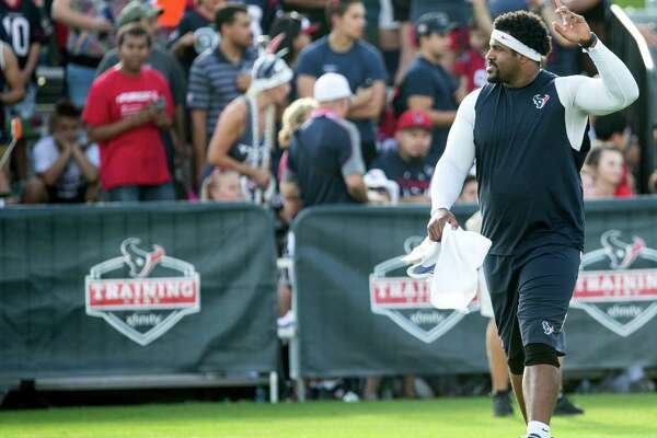 Houston Texans tackle Duane Brown waves at the fans as he walks onto the field during a joint training camp practice between the Texans and the New Orleans Saints at Houston Methodist Training Center on Thursday, Aug. 18, 2016, in Houston.