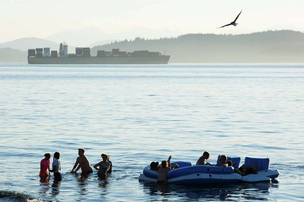 A container ship trudges through the Puget Sound, seen from Alki Beach on July 27, 2016.